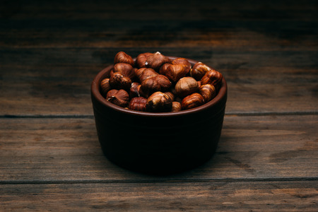 bowl full of hazelnuts on a wooden table