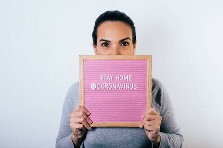 Woman holding sign in her hands with word stay home due to coronavirus