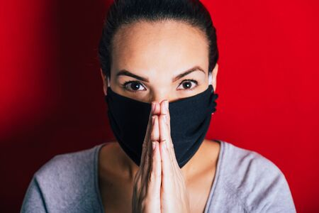 Woman with mask praying for the elimination of the coronavirus pandemic.