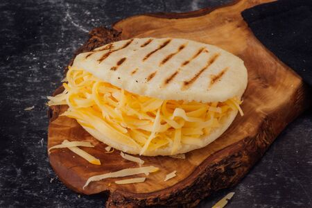 Arepa with yellow cheese on a wooden board