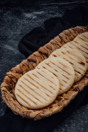 Top view of woven basket filled with a group of Latin American arepas on a dark background