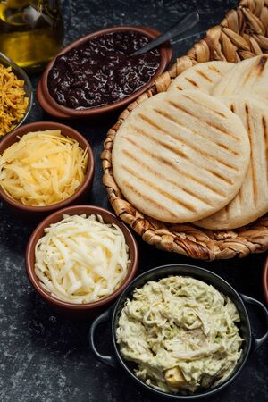 Top view of typical Latin American food. Group of arepas and different types of ingredients to fill them