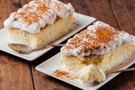 Two pieces of a delicious three milk cake dessert on a wooden background 版權商用圖片
