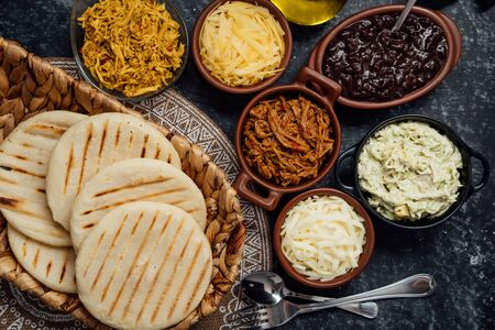 Latin arepas with various ingredients around such as meat, chicken, cheese, black beans and queen pepeada