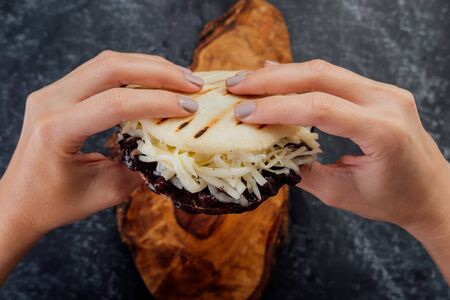 Woman holding a domino arepa.