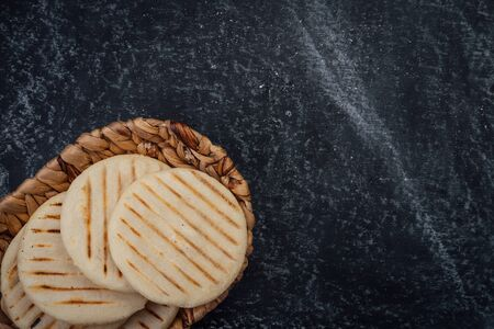 Top view of woven basket filled with a group of Latin American arepas on a dark background, the image has a space to place texts and logos Stok Fotoğraf