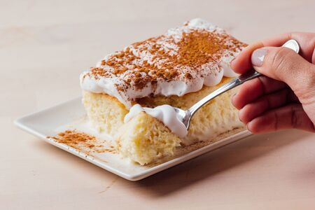 Woman's hand picking up a delicious piece of three milk cake, Latin American dessert