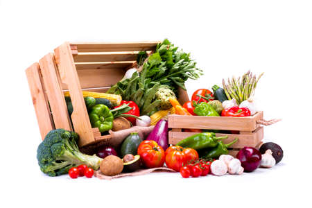 Pine boxes full of fresh vegetables on a white background, ideal for a balanced diet, has tomato, broccoli, potato, avocado, mushrooms, pepper, corn, asparagus, carrot, zucchini Stock Photo