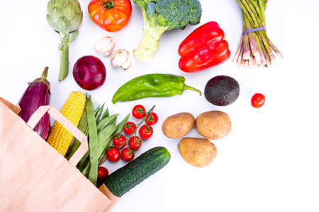 Top view of Paper bag with fresh vegetables on white background, grocery shopping