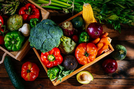 Top view of colorful fresh farm vegetables on a wooden table, balanced diet