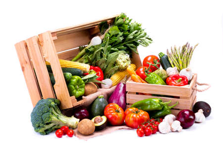 Wooden boxes full of fresh vegetables on a white background, ideal for a balanced diet Stock Photo