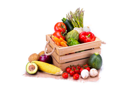 Wooden box full of colorful and fresh vegetables for a balanced and healthy diet on white background, healthy food Stock Photo