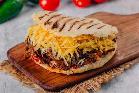 Delicious arepa of shredded meat with yellow cheese Stock Photo