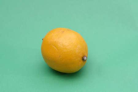 fruited: one lemon on green background Stock Photo