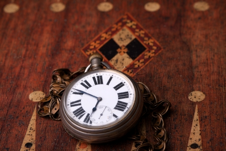 pocket watch on a backgammon table
