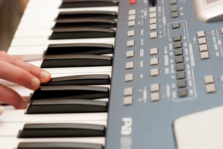 synthesiser: Hands above keys of the piano