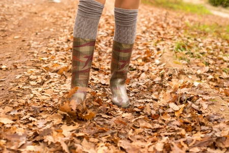 girl in boots walking on a leaves photo