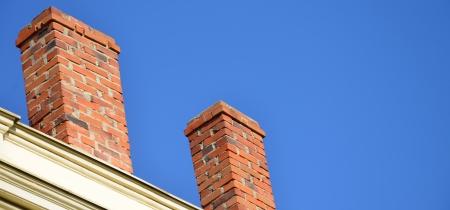 Orange brick pipe and black roof on blue sky Standard-Bild