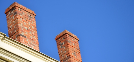 Orange brick pipe and black roof on blue sky Banque d'images