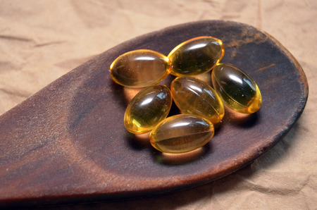Fish oil capsules on a wooden spoon