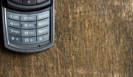 old cell phone: Old cell phone on a wooden background Stock Photo