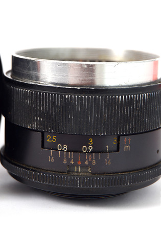 An Old Manual Control Camera Lens Isolated On WhitePicture of a