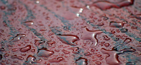 table surface: raindrops on a red table surface, photo of