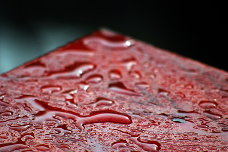 table surface: raindrops on a red table surface photo of