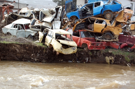 scrap trade: car wrecks near troubled water of a river