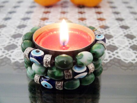 evil eye: Picture of a Burning candle with evil eye amulet decoration