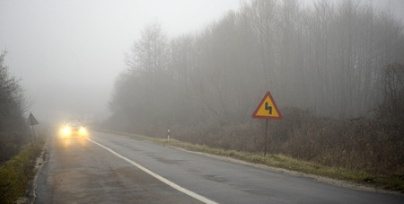 express lane: Picture of a Car appearing through fog with headlights on