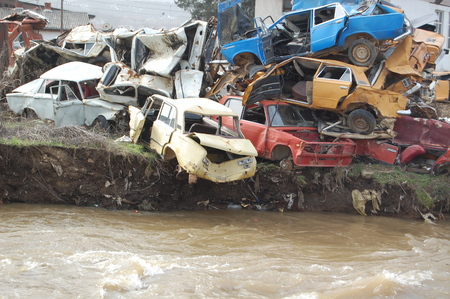 scrap trade: picture of an old wrecked and rusty cars near river