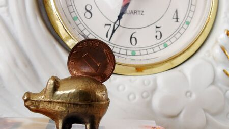 against the clock: Coin on   vintage piggy bank against clock