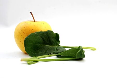 yellow apple: Picture of a Spinach and yellow apple on white background