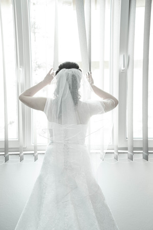 courtain: Bride on a window looking for a groom. Wedding concept