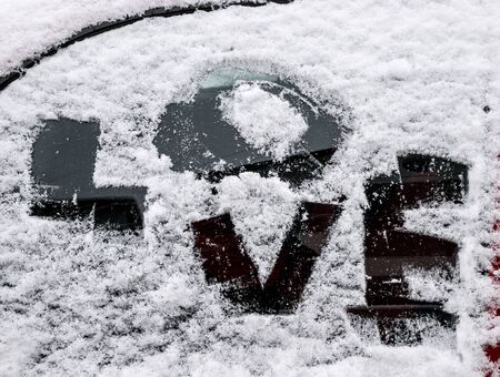 hand cartoon: Picture of a text love on a  frosty car window