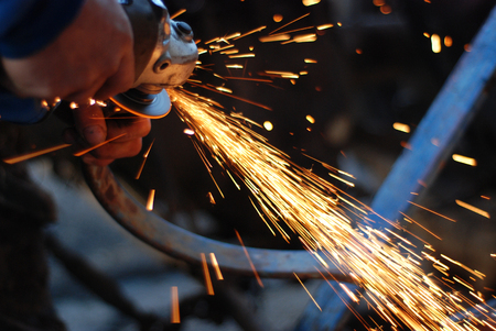 tool and die: Picture of a hands of a worker  while grinding metal