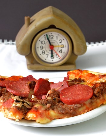 face close up: Picture of a Time for fresh prepared Pizza. Fast food concept