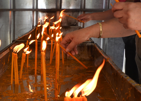 Picture of a People burning candles in an otrhodox church