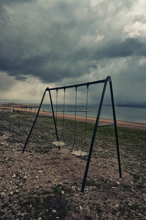 lonliness: Picture of a swing set on a beach of lake prespa, macedonia