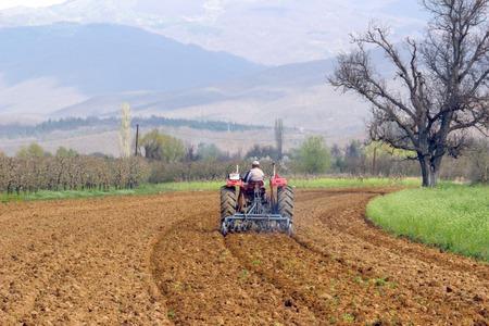arando: imagen de un hombre en tractor arando campo en primavera