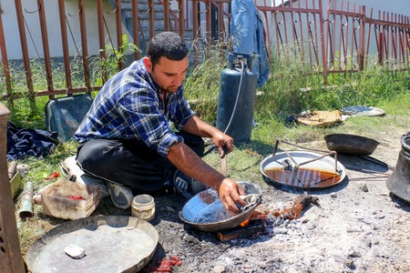 hydrochloric: RESEN, MACEDONIA. MAY 18 , 2016- Young  traveling artisan retinning old copper dish in village of Carev Dvor,Resen,  Macedonia