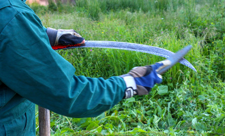 picture of a farmer sharpening scythe to mow the lawn traditionally Stock Photo
