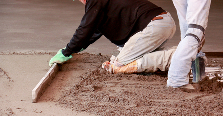 grading: Picture of a Concreting the floor of a house. motion blur on grading tool and hands. Stock Photo