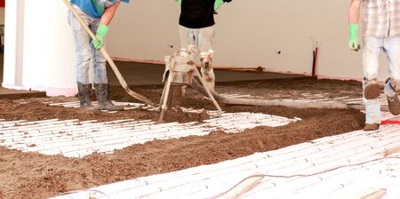 concrete surface finishing: Picture of a Concreting the floor of a house. motion blur on grading tool and hands. Stock Photo
