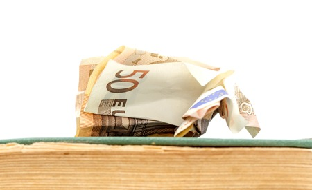picture of a euro banknote od an old weathered book. education cost