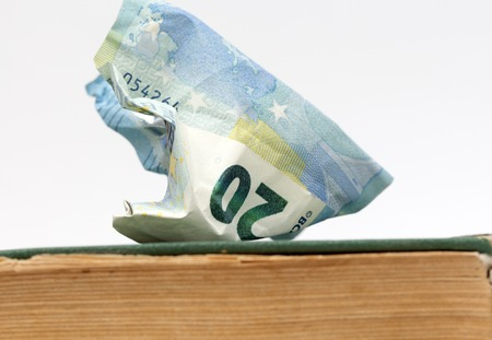 fondo de graduacion: picture of a euro banknote od an old weathered book. education cost