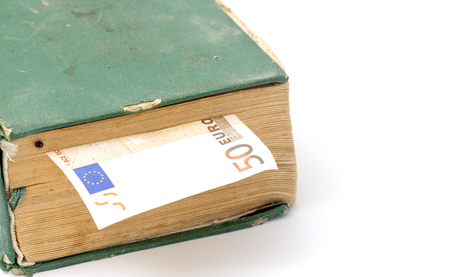 cost of education: picture of a euro banknote od an old weathered book. education cost