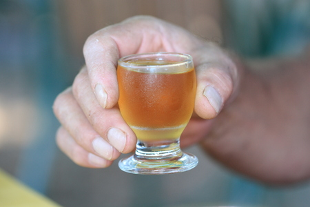 rakia: cheers with famous cold served macedonian yellow rakia glass in a worker hand