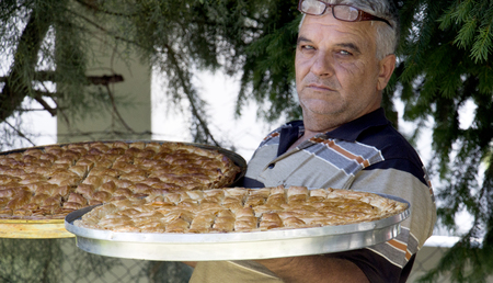 fresh baked: picture of a man holding two platters with fresh baked baklava Stock Photo